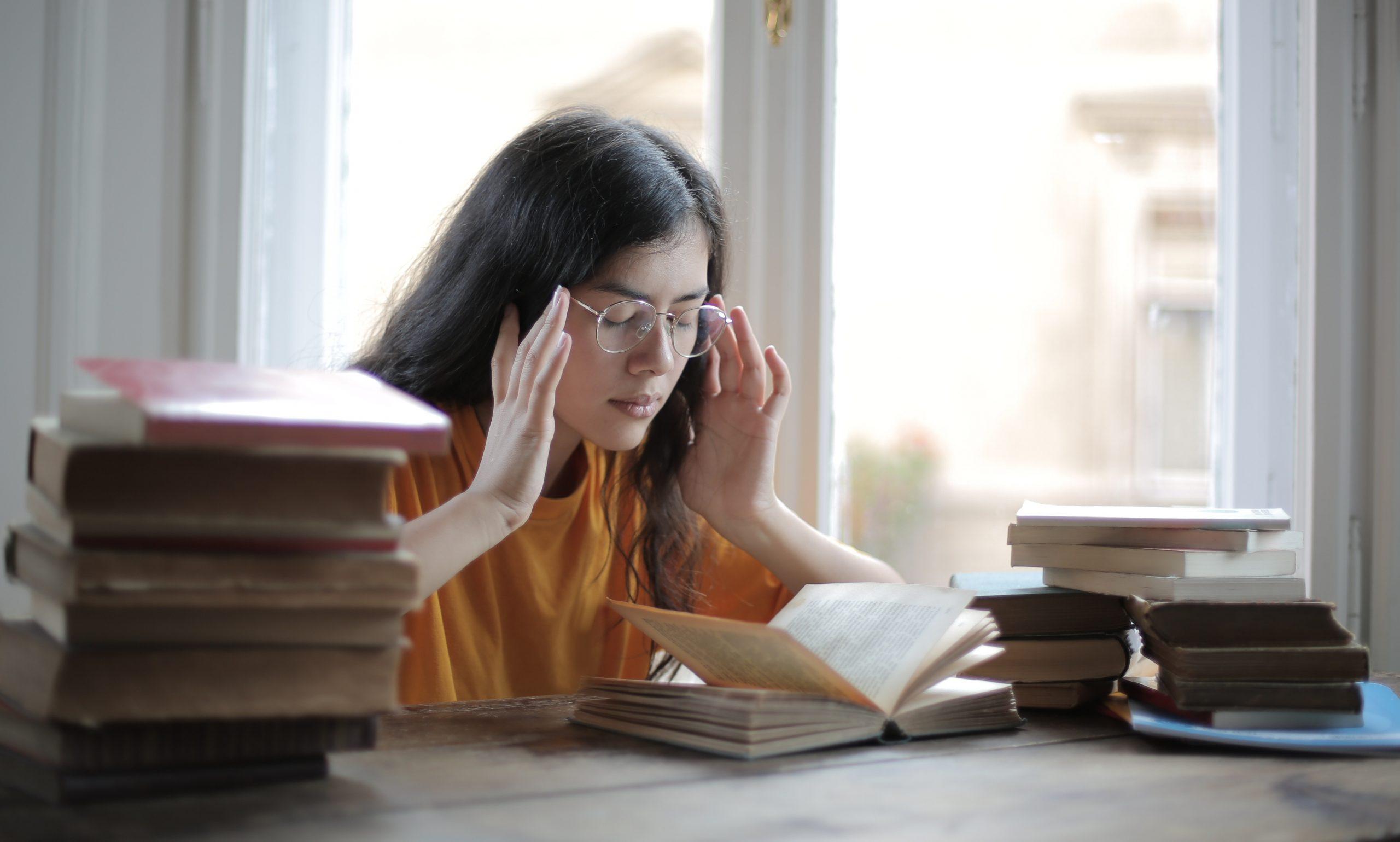 Mulher sentada em uma mesa. Livros sobre a mesa. A mulher está tentando focar.