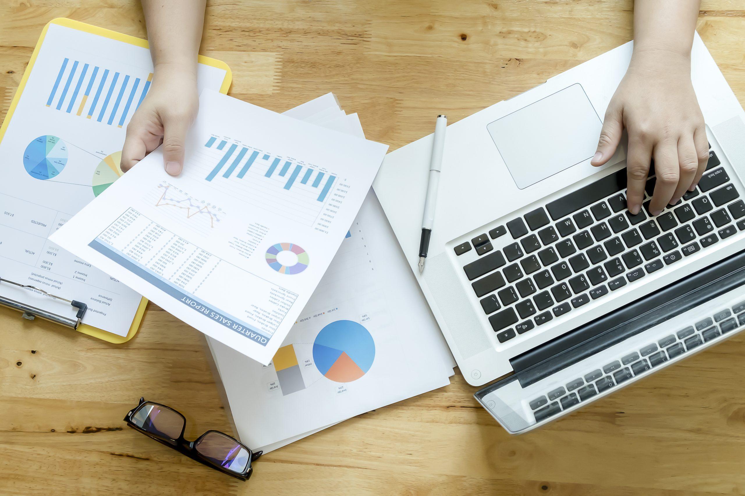 À esquerda da imagem, papéis e um óculos sobre a mesa. A mão de um homem segura um papel onde existem gráficos. À direita da imagem, o mesmo homem toca em um notebook que está sobre a mesa.
