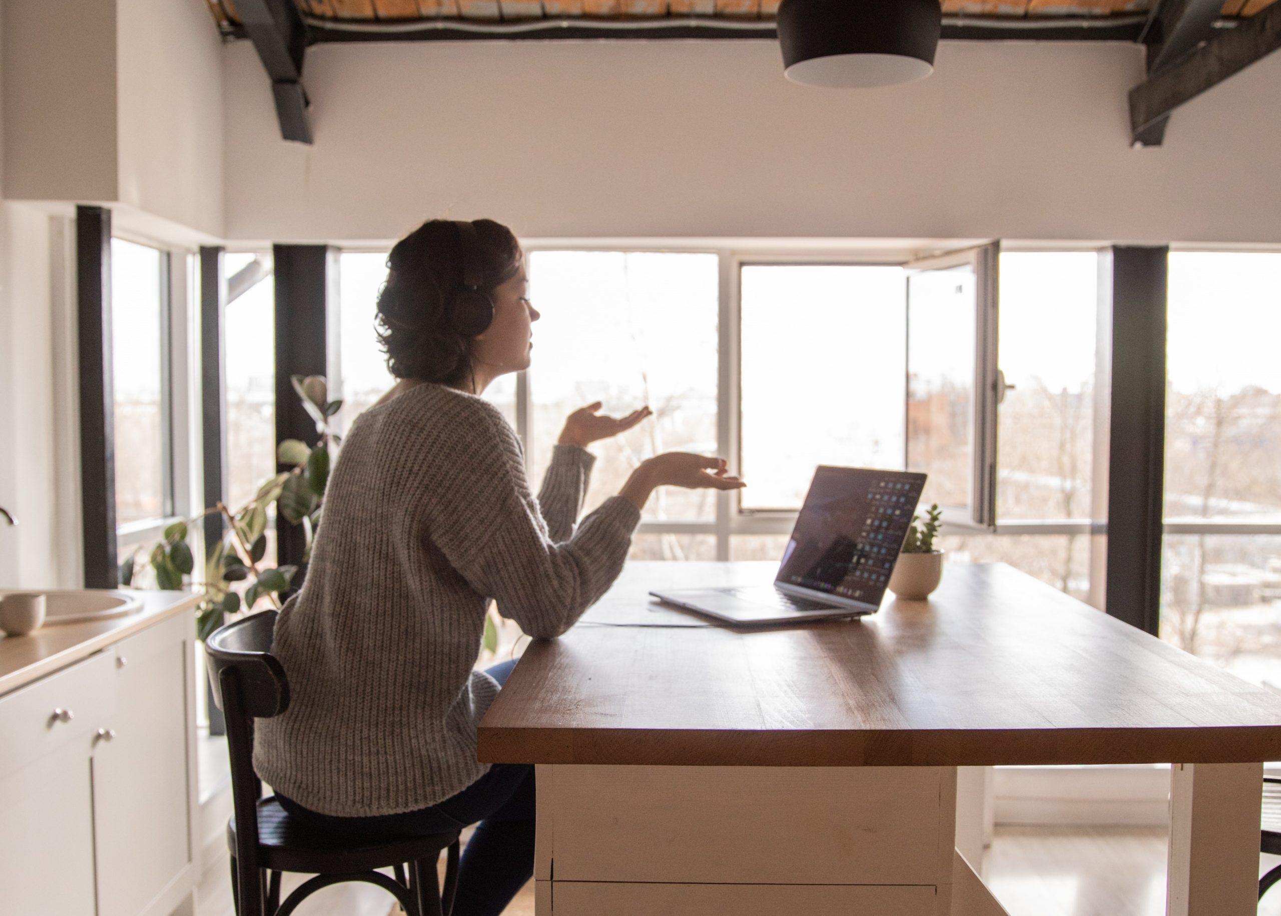 """À esquerda, uma mulher sentada em uma cadeira, gesticulando, falando sobre """"a prevenção do suicídio"""". À direita, um computador aberto sobre uma mesa."""