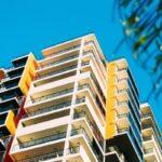 Varandas com fechamento de vidro: entenda sobre as regras. IMG: Prédio das cores bege, amarela e preta com diversas varandas de vidro.