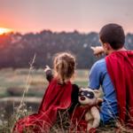 Na esquerda, uma menina vestida de super heroina, com um ursinho no colo. Na direita, o pai, também vestido de super herói, aproveita o por do sol com a filha.